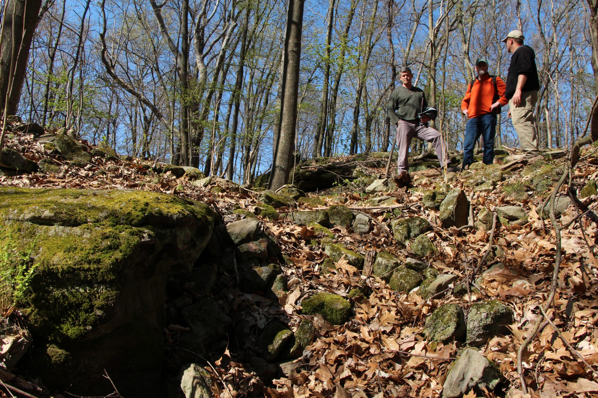 Heartland Earthworks Conservancy board members stand on top of the nearly intact section of the massive stone wall at Glenford Fort
